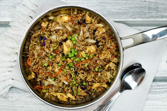 Healthy fried rice in a skillet with fresh scallions.