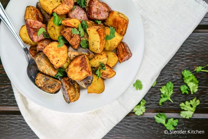 Crispy roasted potatoes with a spoon on a dish.