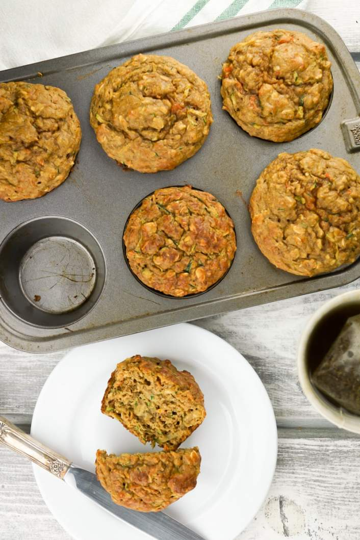 Zucchini and carrot muffins on a plate with a knife.