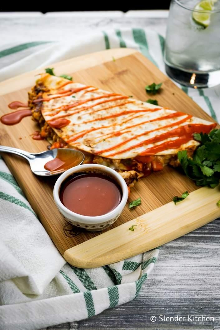 Buffalo Chicken Quesadillas on a cutting board with blurred background.