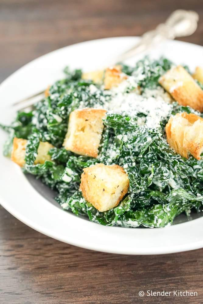 Kale Caesar Salad recipe on a white plate with a wooden background.