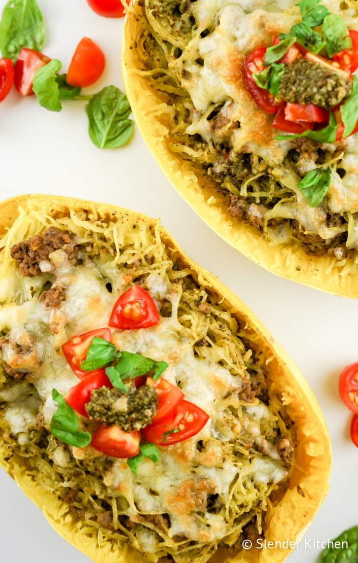 Pesto Spaghetti Squash in a hollow squash with tomatoes and basil.