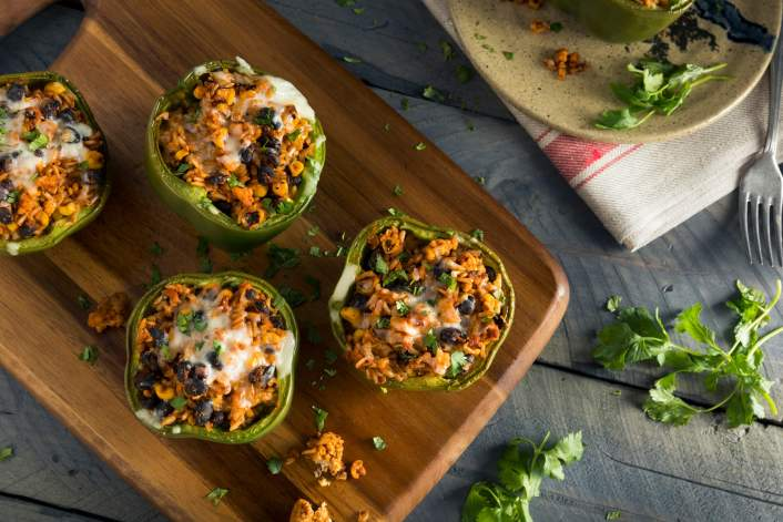 Vegetarian stuffed peppers with corn, black beans, and rice on a cutting board.