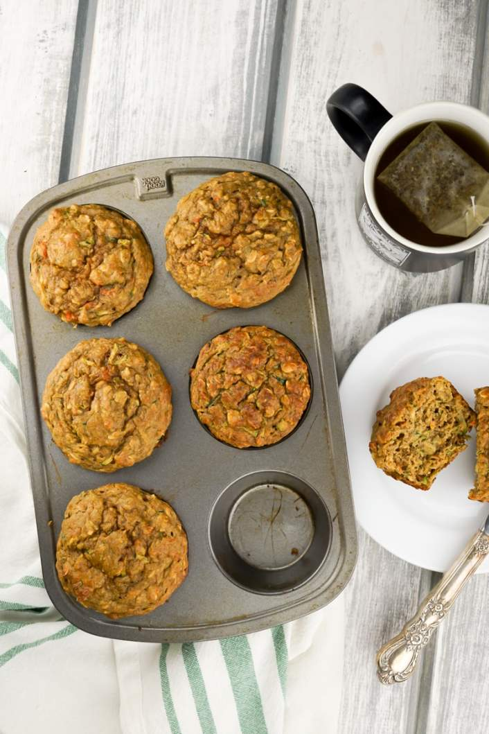 Zucchini Carrot muffins in a muffin tin with a fork.
