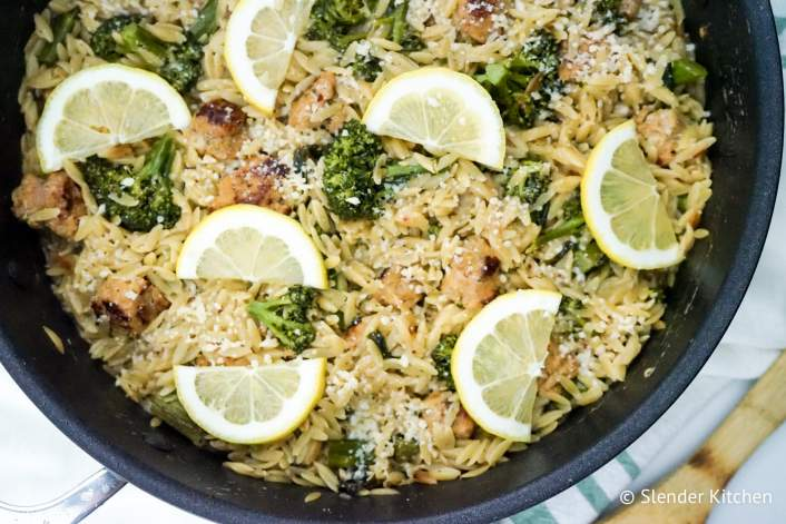 Healthy Lemon Orzo with broccoli, lemon wedges, and chicken sausage in a pan with green napkin.