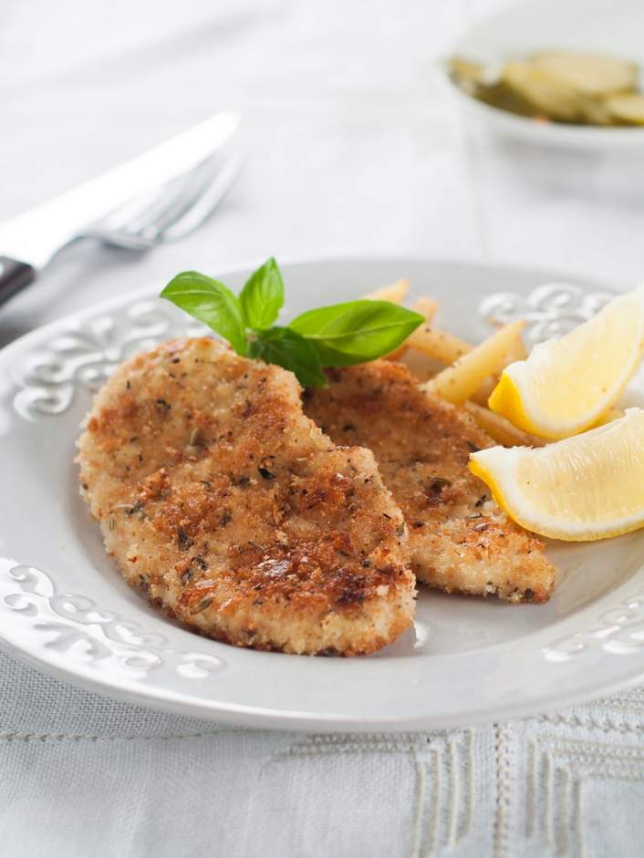 Weight Watchers Crispy Baked Pork with lemon wedges on a white plate.