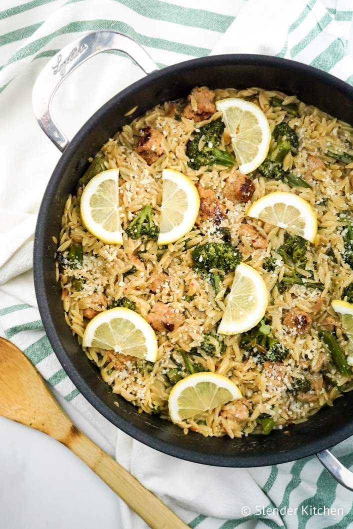 Weight Watchers Lemon Orzo with broccoli and chicken sausage in a pan with wooden spoon.